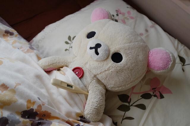 ベッドで熱を測るコリラックマ